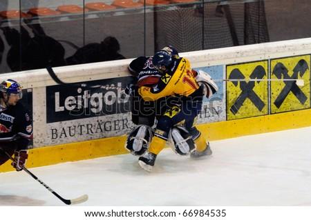 ZELL AM SEE, AUSTRIA - DECEMBER 7: Austrian National League. Putnik charging Goalie Konovalov. Game EK Zell am See vs. Red Bulls Salzburg (Result 4-6) on December 7, 2010 at hockey rink of Zell am See, Austria - stock photo