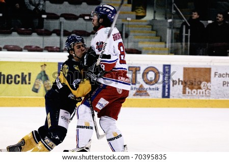 ZELL AM SEE, AUSTRIA - FEB 1: Austrian National League. Brunnegger hits Zell am See player. Game EK Zell am See vs. ATSE Graz (Result 4-1) on February 1, 2011, at hockey rink of Zell am See - stock photo