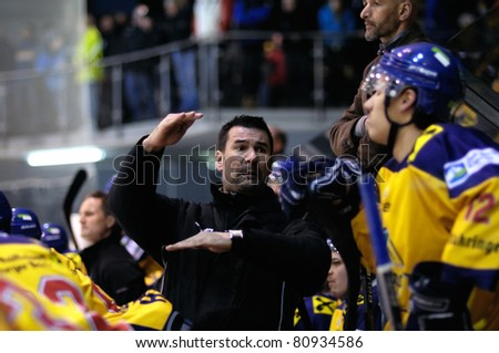ZELL AM SEE, AUSTRIA - FEB 22: Austrian National League. Coach Putnik discussing with players. Game EK Zell am See vs. VEU Feldkirch (Result 3-1) on February 22, 2011 at hockey rink of Zell am See - stock photo