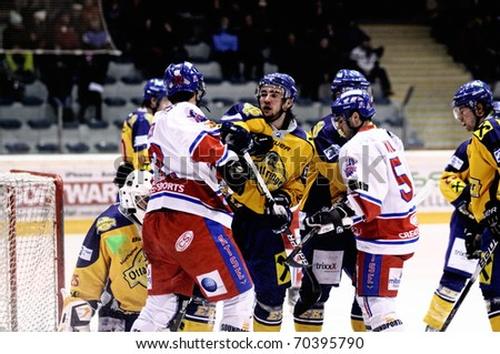 ZELL AM SEE, AUSTRIA - FEB 1: Austrian National League. Graz player gets hit. Game EK Zell am See vs. ATSE Graz (Result 4-1) on February 1, 2011, at hockey rink of Zell am See - stock photo