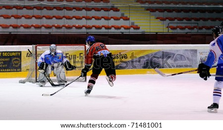 ZELL AM SEE, AUSTRIA - FEB 13: Salzburg hockey League. Niki Lang scores on a breakaway. Game SV Schuttdorf vs HCS Morzg  (Result 9-3) on February 13, 2011 at the hockey rink of Zell am See - stock photo