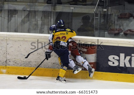ZELL AM SEE, AUSTRIA - NOVEMBER 30: Austrian National League. Graz player gets hit. Game EK Zell am See vs. ATSE Graz (Result 0-4) on November 30, 2010, at hockey rink of Zell am See - stock photo