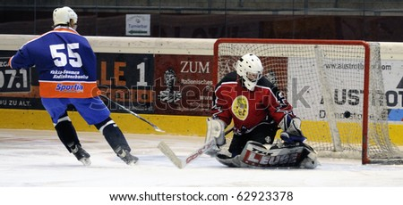 ZELL AM SEE, AUSTRIA - SEPTEMBER 30: Austrian Icehockey Classic Tournament. Aaltonen scores against Goalie Hochwimmer. Zell am See Oldies vs. Pallojussit (3-3) on September 30, 2010 in Zell am See - stock photo