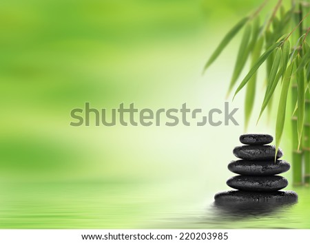 Zen background with stacked stones and bamboo.