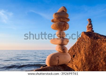 Zen balance of stones at rocky seashore - stock photo
