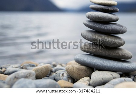 Zen Balancing Pebbles Misty Lake Abstract Peaceful Concept - stock photo