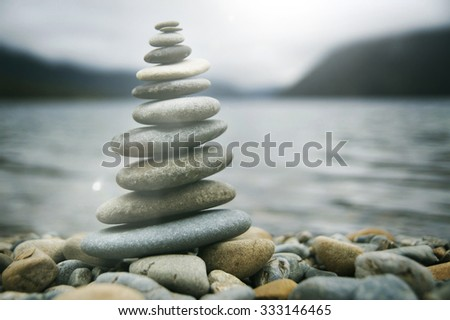 Zen Balancing Pebbles Misty Lake Stone Stack Tranquil Concept - stock photo