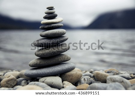 Zen balancing pebbles next to a misty lake.