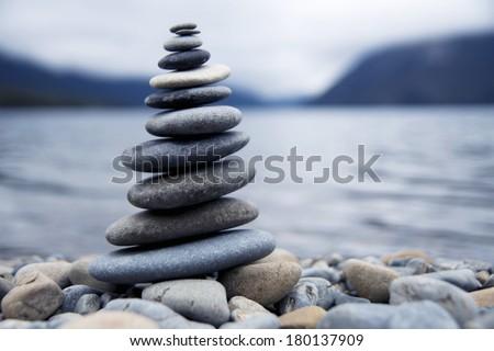 Zen Balancing Rocks Next to a Misty Lake, New Zealand - stock photo