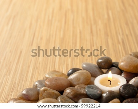 Zen candle in pebbles with wood background