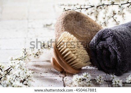 zen detox still-life - body brush and towel over stone, fresh white spring flowers and mineral limestone background for body care spa treatment