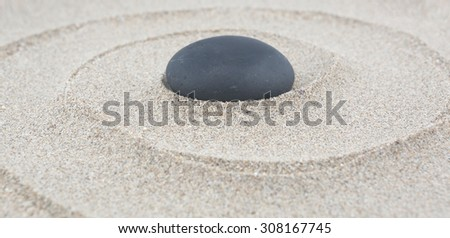 Zen garden - spa stone in the sand. Meditation, spirituality and harmony concept - stock photo