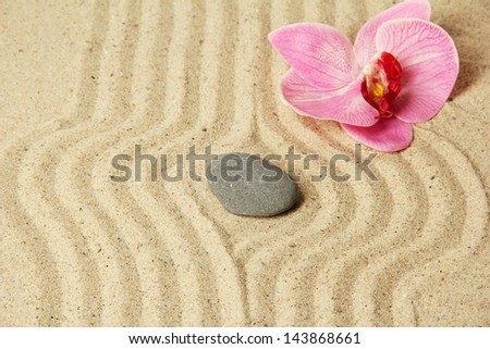 Zen garden with raked sand and round stone close up - stock photo
