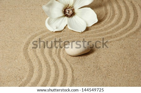 Zen garden with raked sand and round stone close up