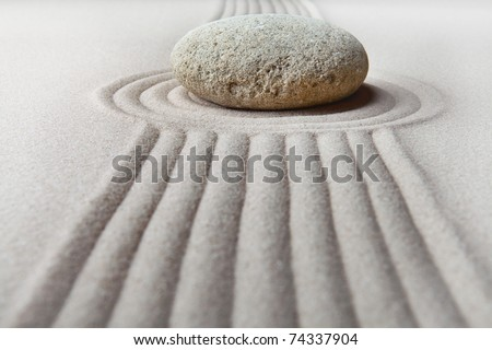 zen garden with raked sand and round stone pattern of ripples and lines create tranquil scene ideal for relaxation and meditation - stock photo