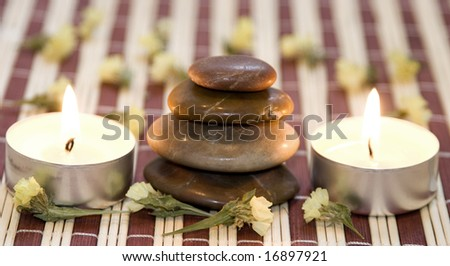 Zen like balanced stones, dried flower and candles on bamboo background.