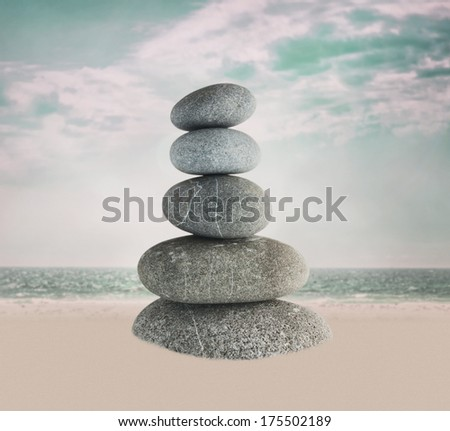 Zen like pebble pyramid against retro style beach background