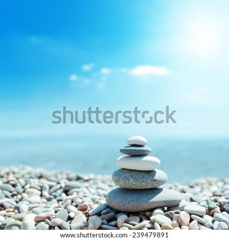 zen-like stones on beach and sun in sky. soft focus on bottom - stock photo