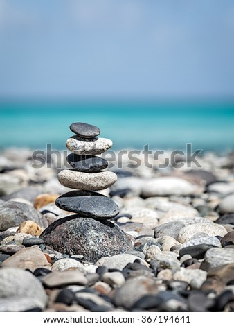 Zen meditation relaxation concept background -  balanced stones stack close up on sea beach - stock photo