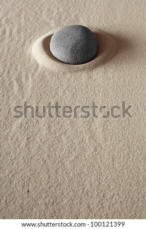 zen meditation stone relaxation or concentration point to focus and to meditate round grey rock in dry sand simplicity and purity spa background abstract concept - stock photo