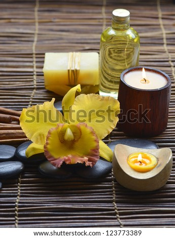 Zen rock and beautiful orchid, candle, soap on mat - stock photo