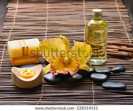 Zen rock and Handmade soap with candle, yellow orchid on mat - stock photo