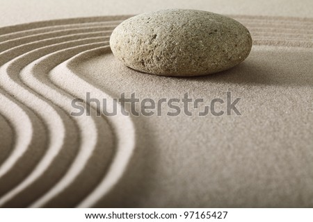 zen rock garden japanese garden zen stone with raked sand and round stone tranquility and balance ripples sand pattern spa relaxation - stock photo