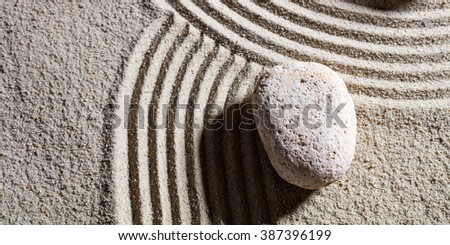 zen sand still-life - one stone at the intersection of different roads for concept of change or flexibility with serenity, top view - stock photo