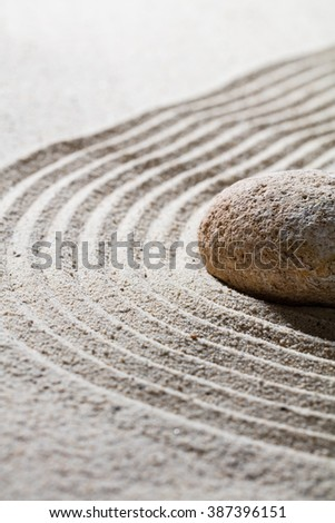 zen sand still-life - textured stone on sinuous waves for concept of relaxation or meditation in beauty or spirituality, closeup - stock photo