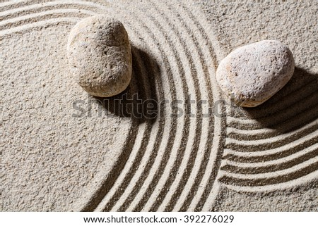 zen sand still-life - two stones across lines to give different directions for concept of change or flexibility with peace, top view - stock photo