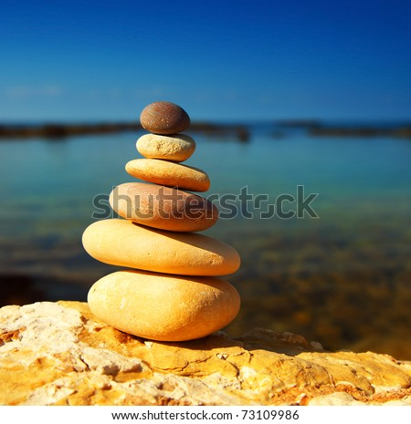 Zen spa balance stones, over blue calm sea background, conceptual image of relaxation & vacation - stock photo