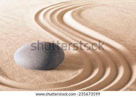 zen stone garden round stone and raked sand making line patterns tranquil scene for relaxation and meditation simplicity and balance are the base of a Japanese garden nice calm spa background  - stock photo