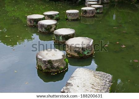 Zen stone path in the Japanese Garden of Heian-jingu Shrine. - stock photo