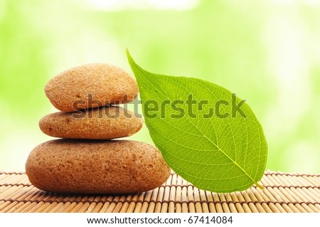 zen stone with leaf and bokeh copyspace showing spa concept - stock photo