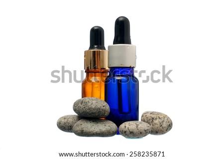 Zen stone with spa oil on white background - stock photo