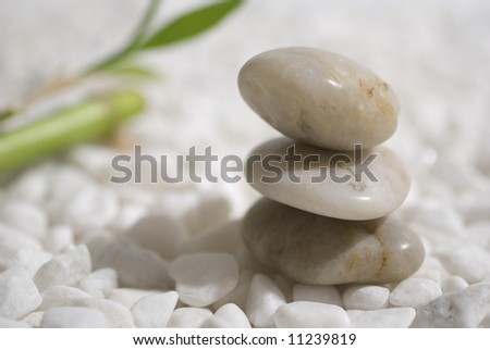 zen stones and bamboo on white pebbles background - meditation concept - stock photo