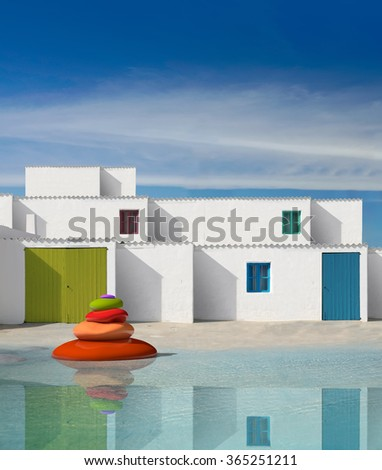 zen stones and facades of houses with white wall and painted wooden doors - stock photo