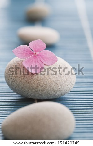 Zen stones and pink flowers on blue bamboo mat - stock photo