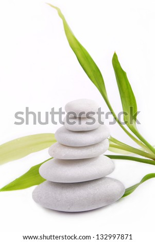 Zen stones isolated on white background with bamboo - stock photo
