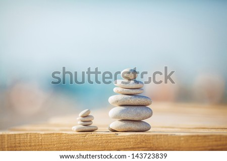 zen stones on wooden banch on the beach near sea. Outdoor. en style path on vintage wood table in relaxing wellness holistic spa for relaxation and good health rejuvenation - stock photo