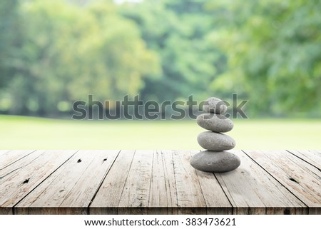 zen stones on wooden in the garden. vintage wood table in relaxing wellness holistic spa for relaxation and good health rejuvenation. stones stacked on wooden table outdoors. - stock photo