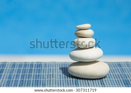 Zen stones one above the other on blue bamboo straw mat  - stock photo