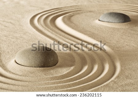 zen stones or rocks and raked lines in sand Japanese stone garden for meditation. Purity balance and spirituality background. Spa wellness massage rock therapy  - stock photo