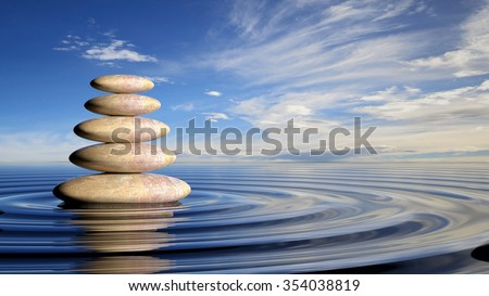 Zen stones stack from large to small  in water with circular waves and peaceful sky. - stock photo