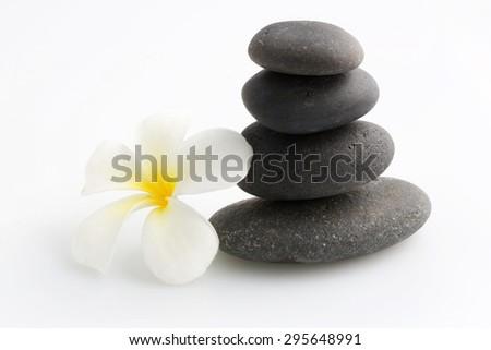Zen stones with frangipani flower on white - stock photo