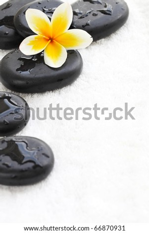 zen stones with frangipani flower on white towel - stock photo
