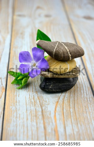 Zen stones with purple flower on old grey used wood