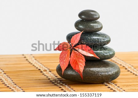 Zen stones with red leaf on a bamboo mat - stock photo
