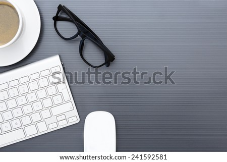 zenithal view of a grey business desk consisting on a wireless silvery keyboard, a wireless mouse, a black eyeglasses and a cup of coffee - suitable for copy space  - stock photo
