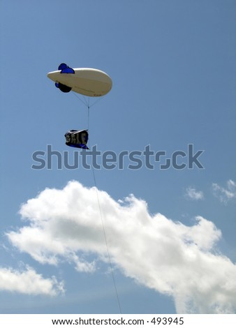 Zeppelin-shaped advertising balloon on blue sky with clouds - stock photo